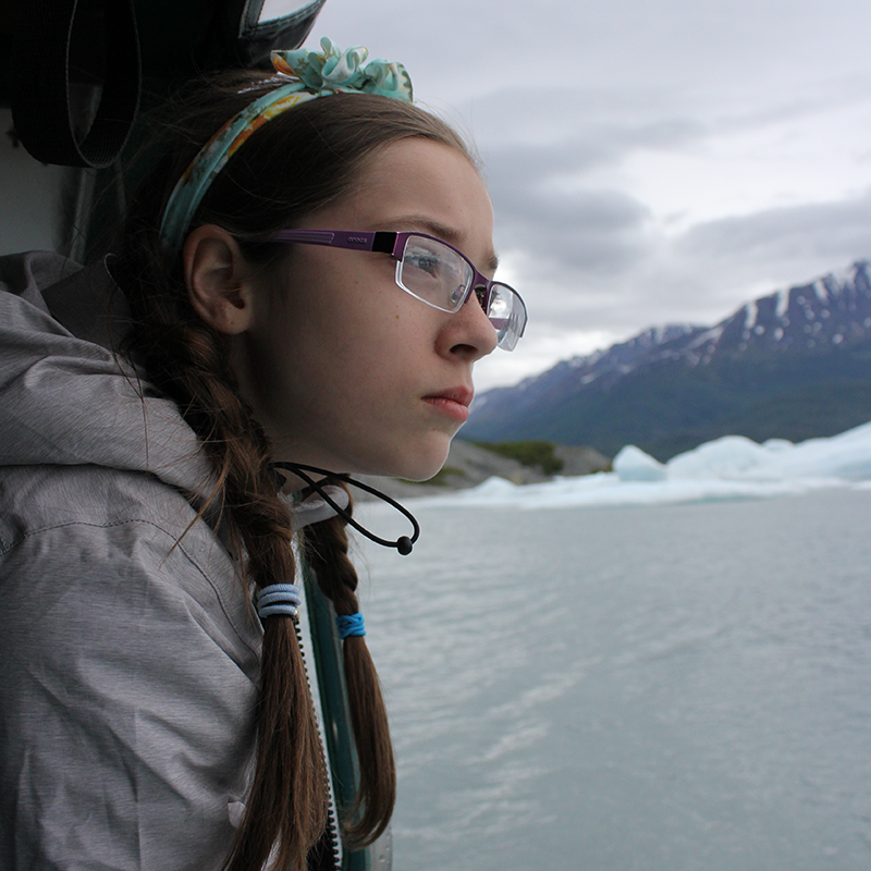 Lesli's daughter gazes out over a river of icebergs on the Knik River, Alaska.